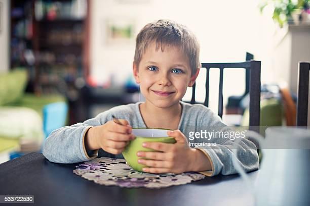 Happy little boy eating breakfast cereal