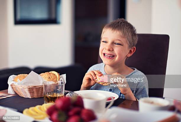 Happy little boy eating breakfast