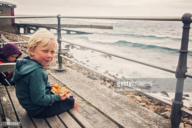 Happy little boy eating fish and chips by the sea