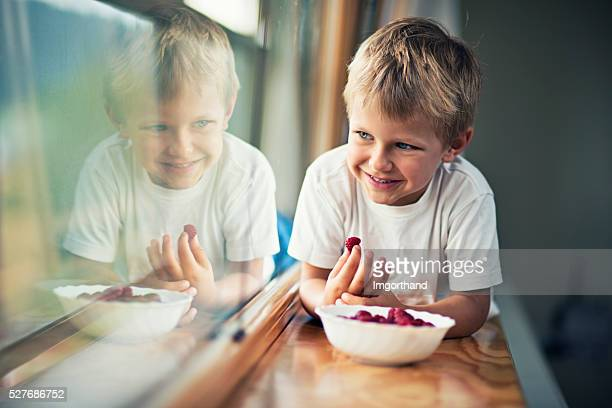 Happy little boy eating raspberries