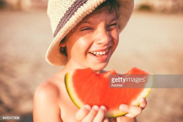 gelukkig jongetje watermeloen te eten op het strand - lagere schoolleeftijd stockfoto's en -beelden