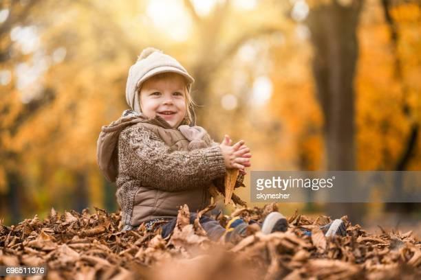Gelukkig jongetje genieten in de herfst bladeren in het park.