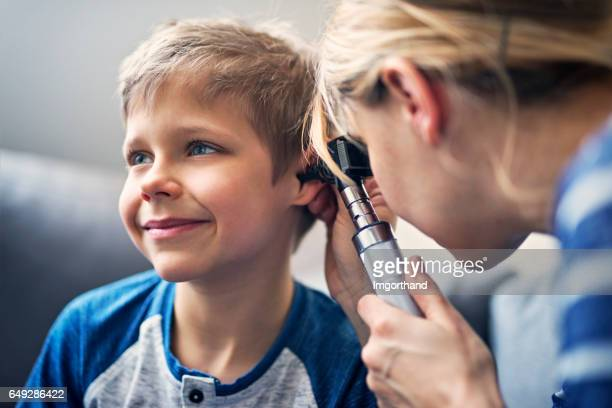Happy little boy having ear exam
