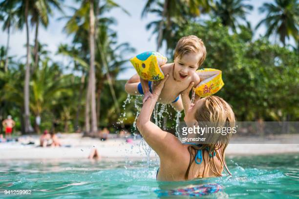 happy little boy having fun in the sea while being held by his mother. - vacations stock pictures, royalty-free photos & images