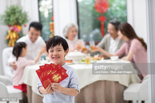 happy little boy holding many red envelopes - religious celebration stock pictures, royalty-free photos & images