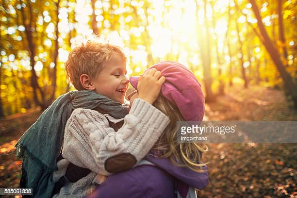 Happy little boy hugging his mother in autumn forest