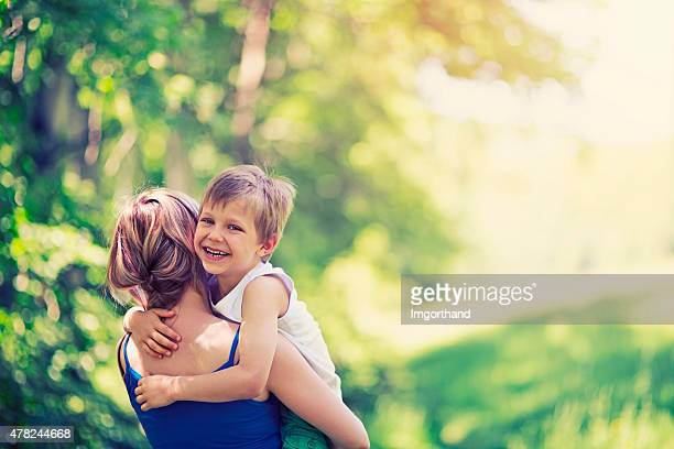 Happy little boy hugging his mother in forest