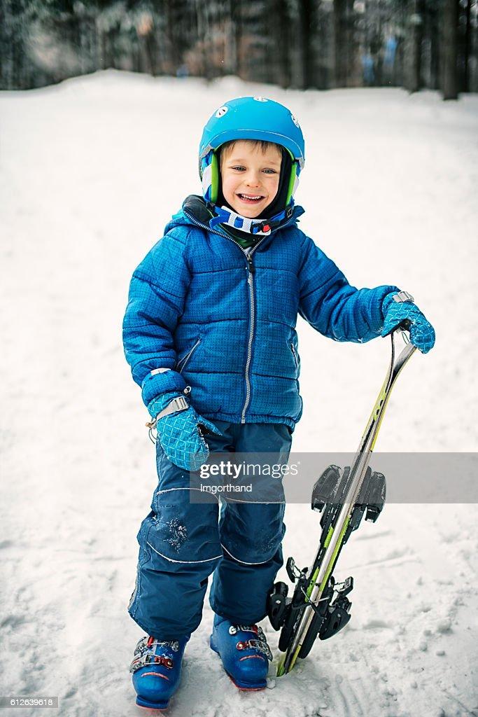 65ace94d8d6e Happy Little Boy In Winter Wearing Ski Gear Holding Skis Stock Photo ...