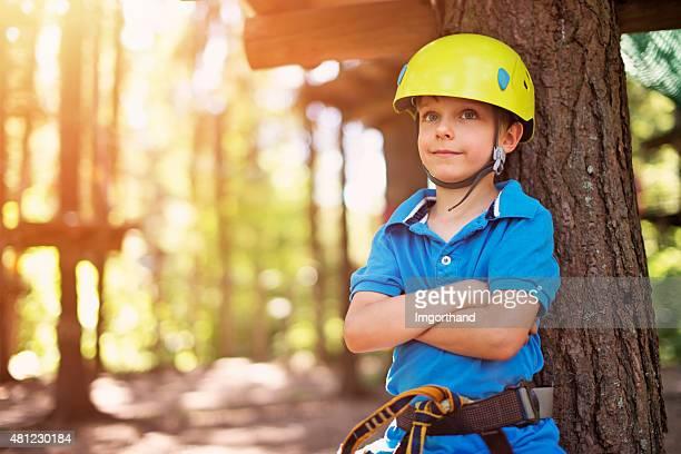 Happy little boy in zip line adventure park