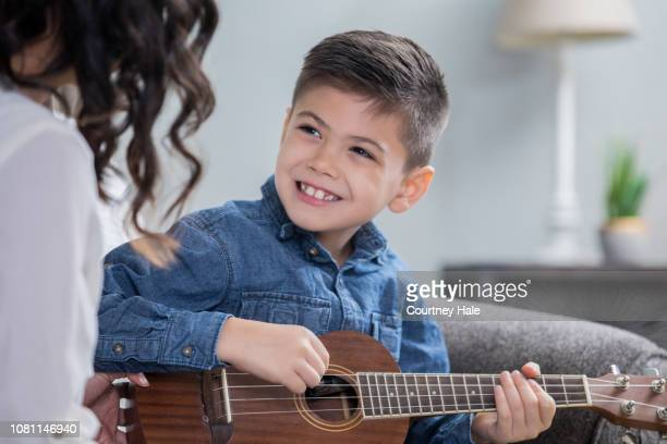 happy little boy is practicing   playing ukulele during a private music lesson with mother or teacher - ukulele stock pictures, royalty-free photos & images