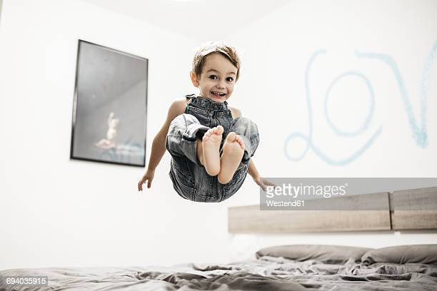 Happy little boy jumping on the bed