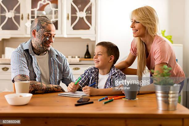 Happy little boy laughing with his parents at home.