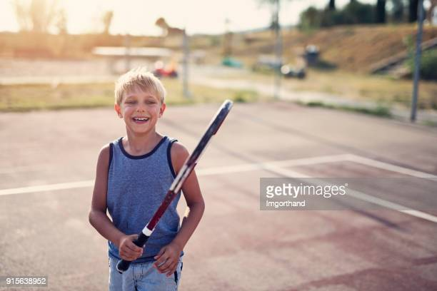 Happy little boy learning to play tennis