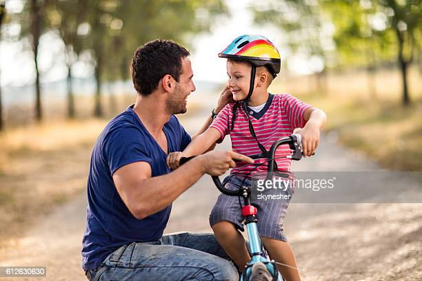 Happy little boy on bike taking with father in nature.