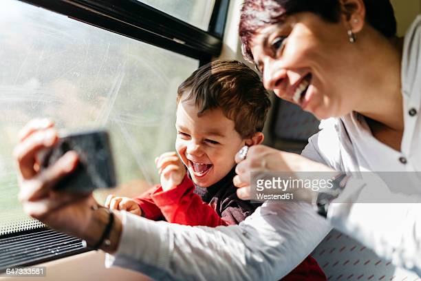 Happy little boy on his first train ride having fun with his mother