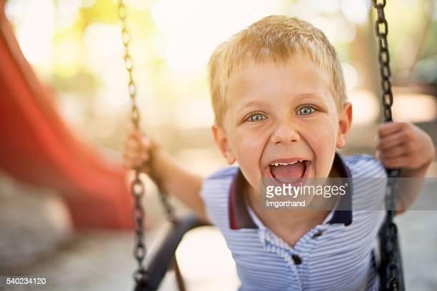 Happy little boy on swing