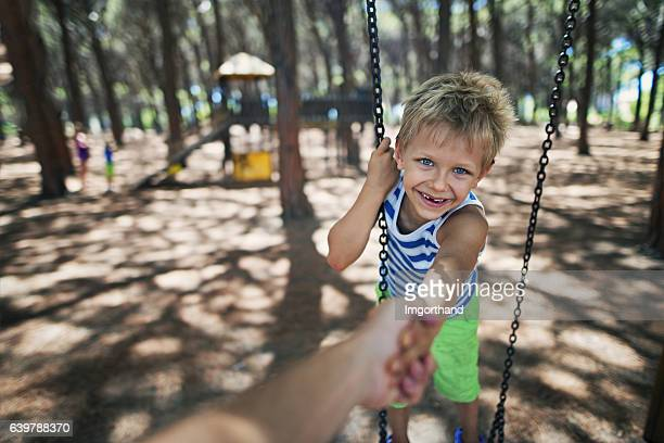 Happy little boy on swing pulled by father