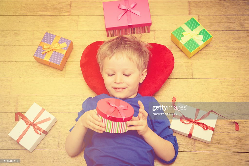 Happy little boy opening presents on holiday : Stock Photo