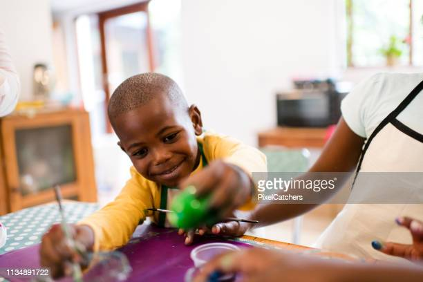 happy little boy painting green easter eggs - easter religious stock pictures, royalty-free photos & images