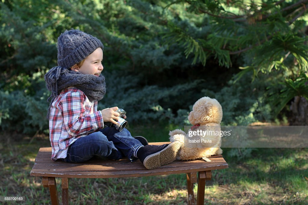 Happy little boy photographing his teddy bear : Foto stock