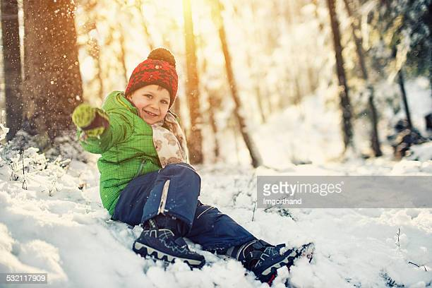 Happy little boy playing in winter forest