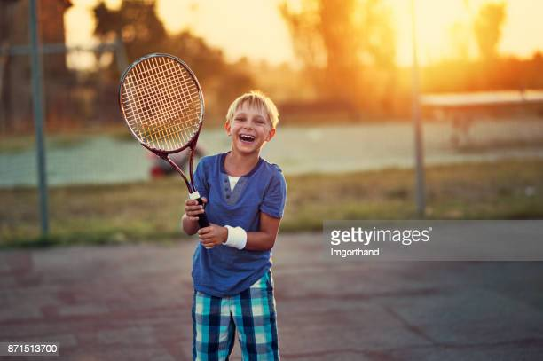 happy little boy playing tennis - tennis stock pictures, royalty-free photos & images
