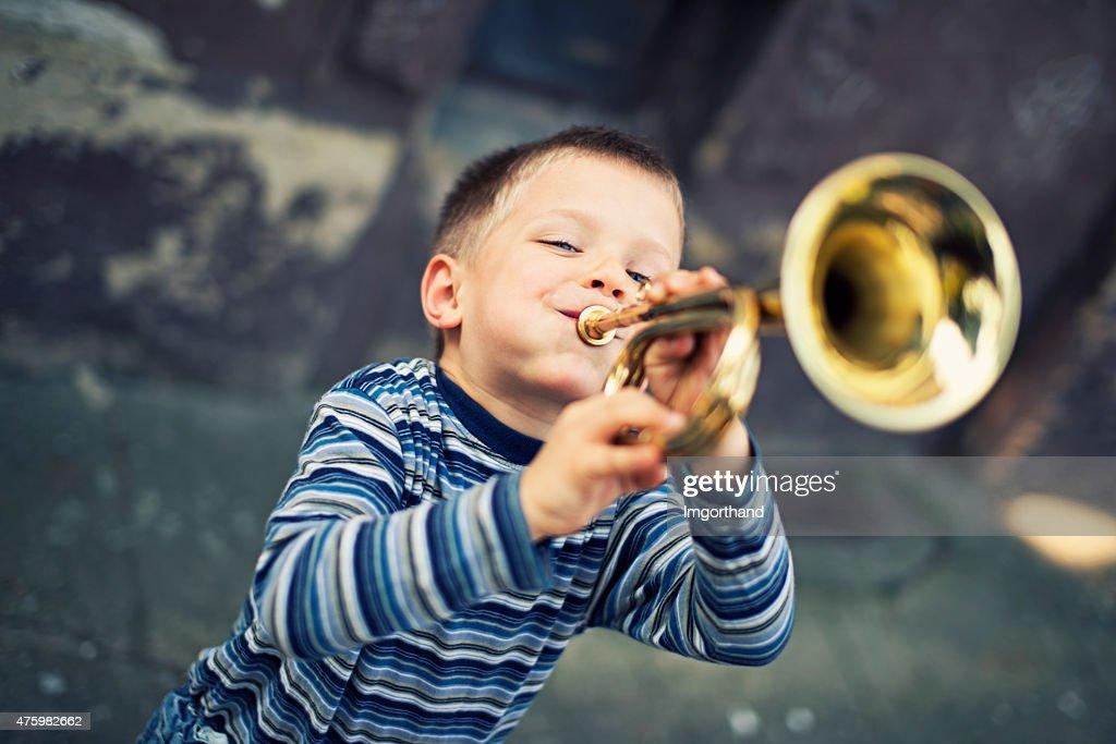 Glücklich kleiner Junge spielt Trompete : Stock-Foto