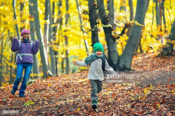 Happy little boy playing with mother in autumn forest
