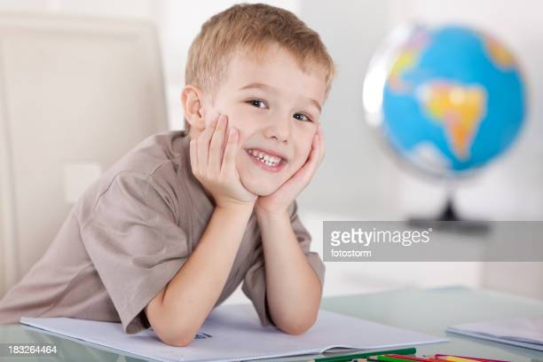 Happy little boy relaxing in the classroom