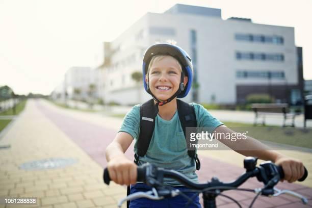 glückliche kleine junge reiten fahrrad in modernes wohngebiet - 8 9 jahre stock-fotos und bilder