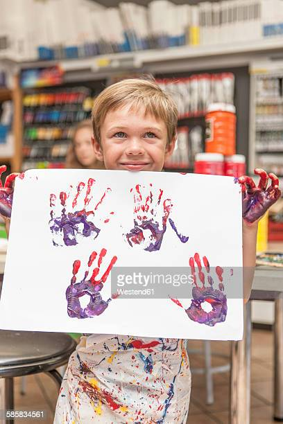 Happy little boy showing his picture in an art class