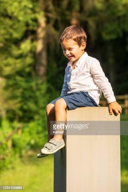 glücklicher kleiner junge sitzt draußen auf einem betonblock - kemter stock-fotos und bilder