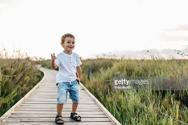 Happy little boy standing on boardwalk in nature