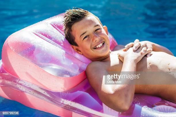 glückliche kleine junge im pool - knaben in badehosen stock-fotos und bilder