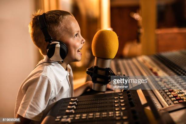Happy little boy talking on a microphone in a radio station.