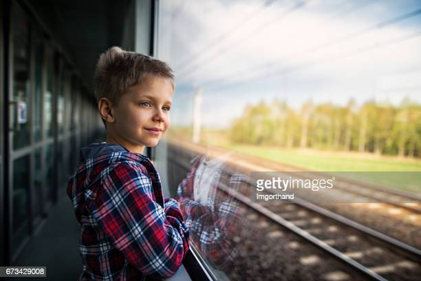 Happy little boy travelling on train