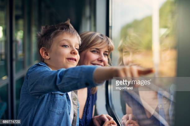 Happy little boy travelling on train with mother