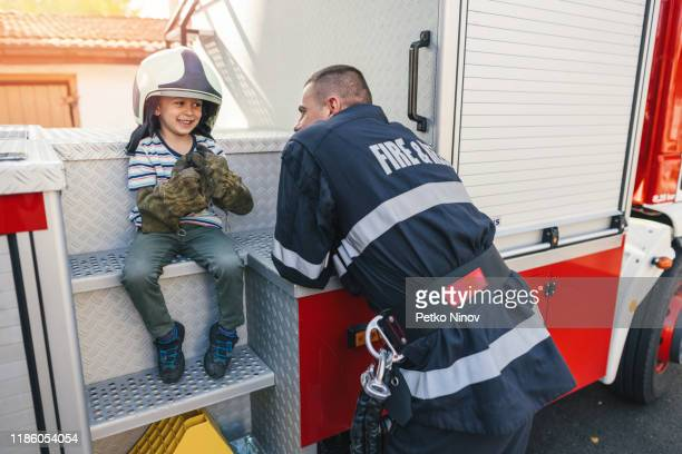 happy little boy visiting the firefighters - fire protection suit stock pictures, royalty-free photos & images