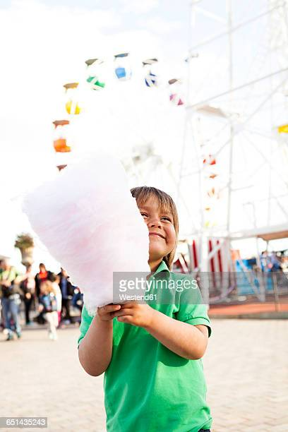 Happy little boy with cotton candy on fair