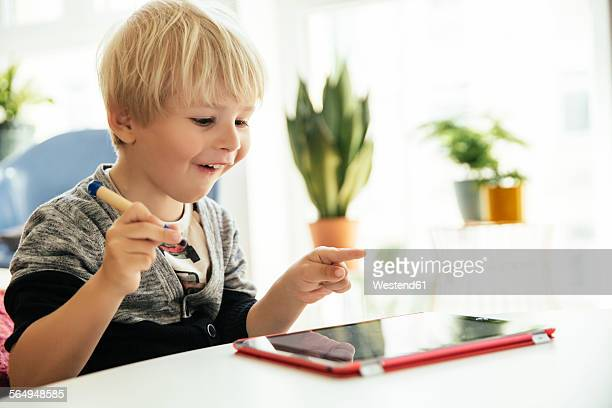happy little boy with digital pen and digital tablet at home - guardare verso il basso foto e immagini stock