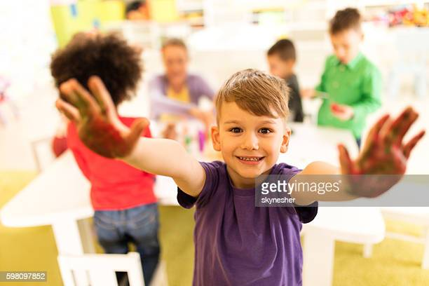 Happy little boy with raised hands having fun at preschool.