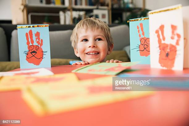 Happy little boy with self-made Easter cards at home