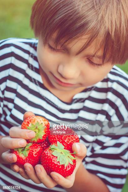Happy little boy with strawberry