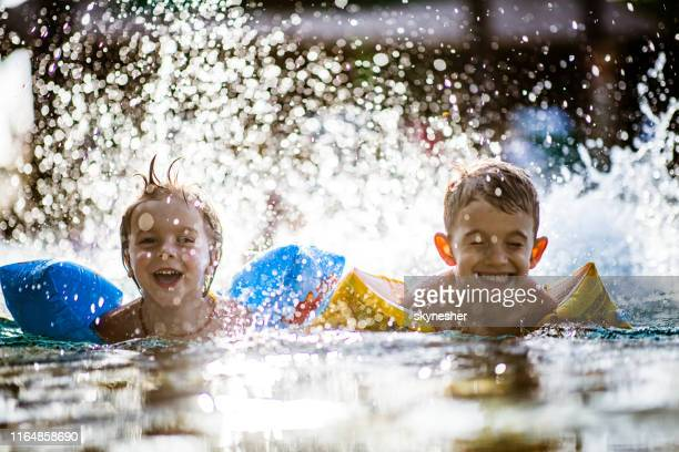 happy little boys having fun while splashing water in summer day. - arm band stock pictures, royalty-free photos & images