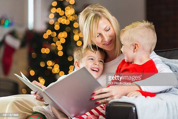 Happy little boys listening to mom read Christmas story book