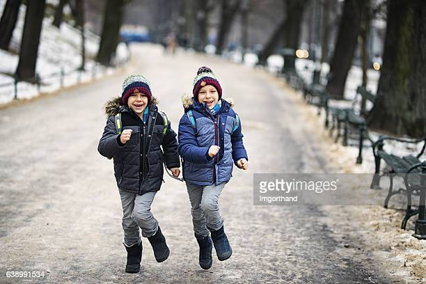 Happy little boys running from school in winter