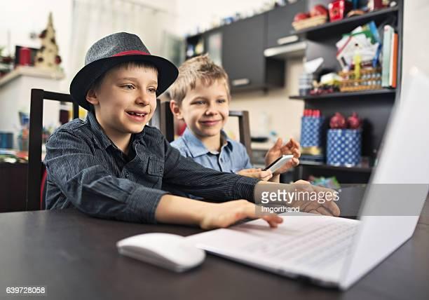 Happy little boys using laptop