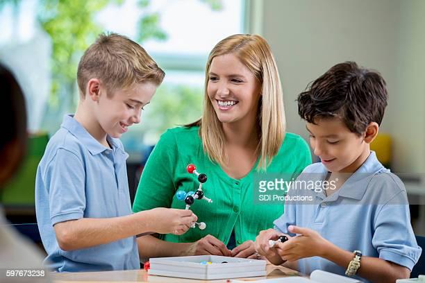Happy little boys using molecule model in science class