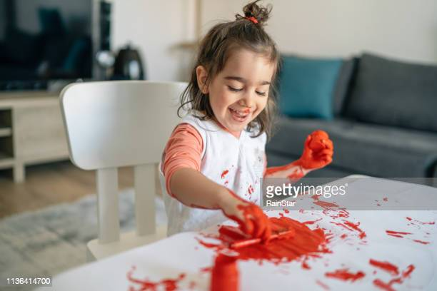 happy little child having fun doing finger painting at home - messy stock pictures, royalty-free photos & images