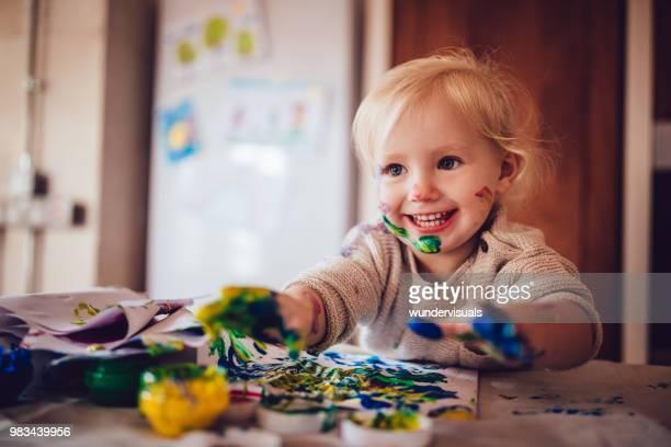 glückliches kleines kind spaß dabei fingermalerei zu hause - kindergarten stock-fotos und bilder